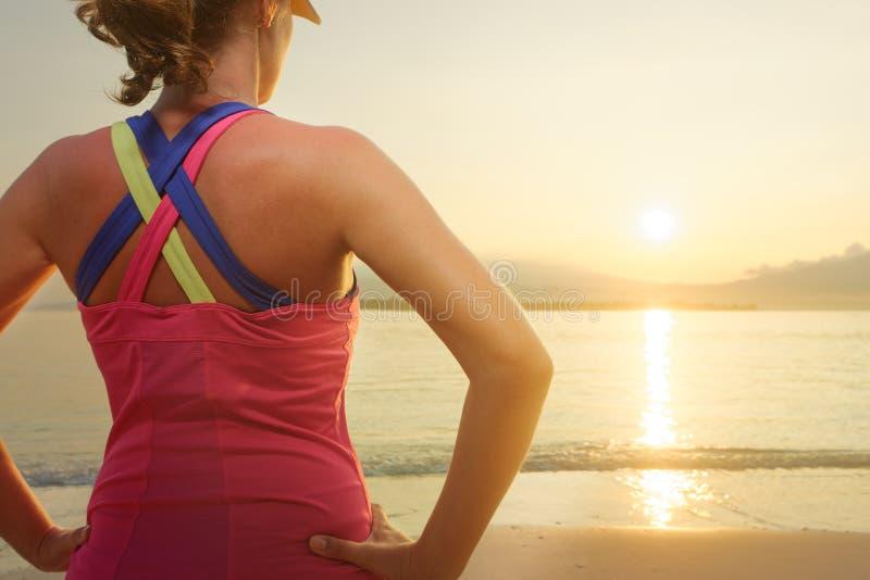 Corredor femenino joven en la playa que mira el océano y la puesta del sol foto de archivo
