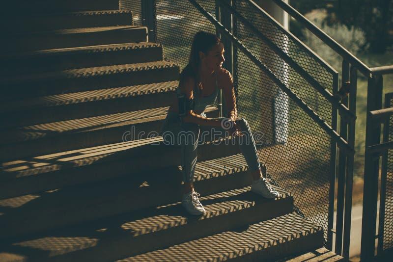 Corredor femenino joven que descansa sobre las escaleras fotos de archivo libres de regalías