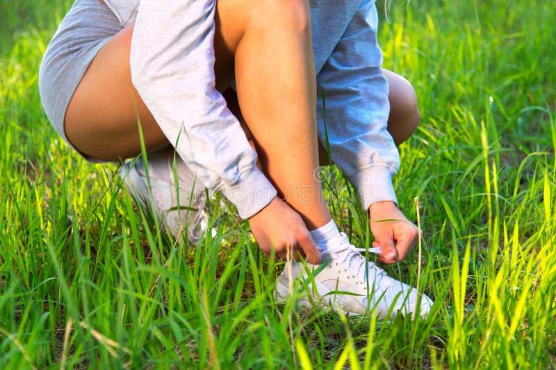 Corredor femenino que ata cordones de zapato en rastro de funcionamiento Primer del corredor femenino de la aptitud del deporte q imagenes de archivo