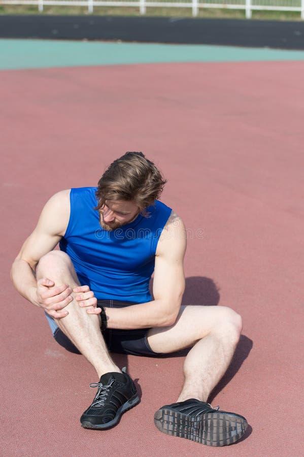 Corredor herido en dolor corriente de la sensación de la pista de la pierna quebrada imagenes de archivo