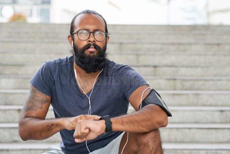 Corredor indio usando Smartwatch imágenes de archivo libres de regalías