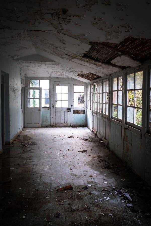 Corredor interior de un hospital abandonado con techo derrumbado y ventanas rotas imagen de archivo libre de regalías