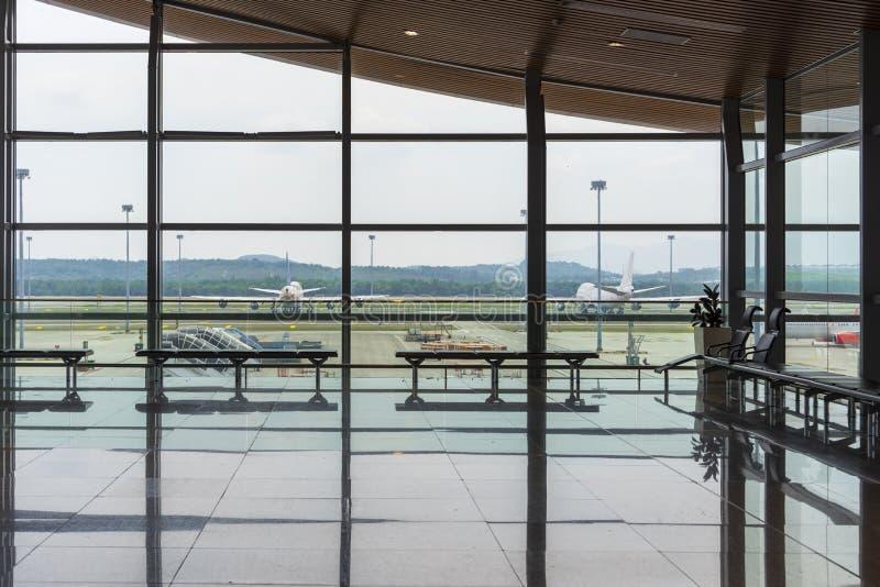 Corredor interior do aeroporto internacional com assentos e a janela de vidro do quadro e das reflexões no salão da partida do te imagem de stock royalty free