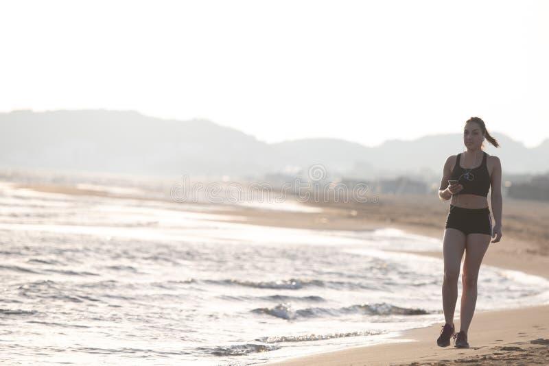 Corredor joven sano de la mujer de la aptitud que corre en la playa tr de la salida del sol foto de archivo libre de regalías