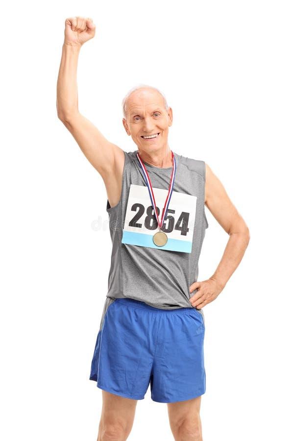 Corredor maduro com a medalha que aumenta seu punho fotografia de stock