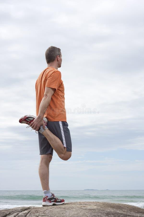 Corredor maduro que hace ejercicios en una playa fotografía de archivo libre de regalías