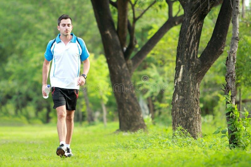 Corredor masculino deportivo que camina cerca en el borde de la carretera mientras que tome una respiración imagen de archivo