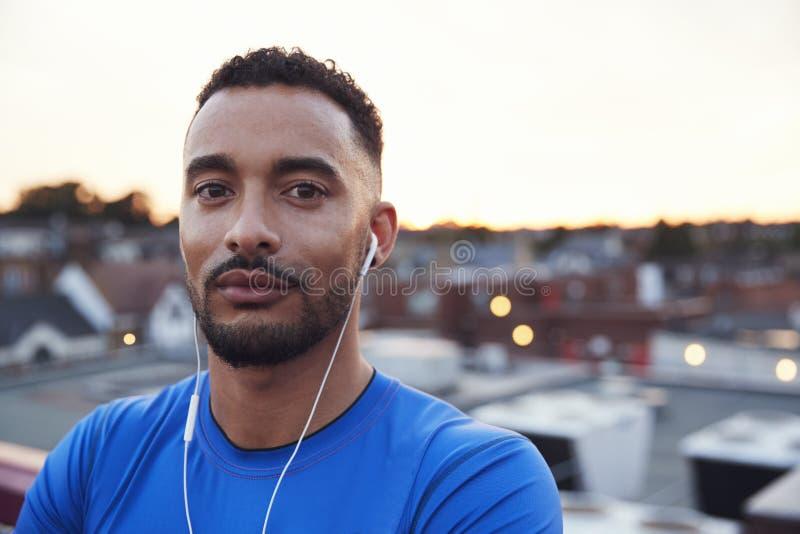 Corredor masculino en el ambiente urbano que mira a la cámara, cierre para arriba imagen de archivo