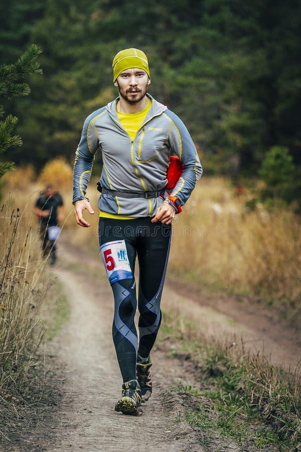Corredor masculino joven que corre a través del camino forestal fotos de archivo libres de regalías