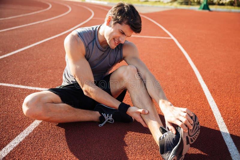 Corredor masculino joven que sufre del calambre de pierna en la pista imagenes de archivo