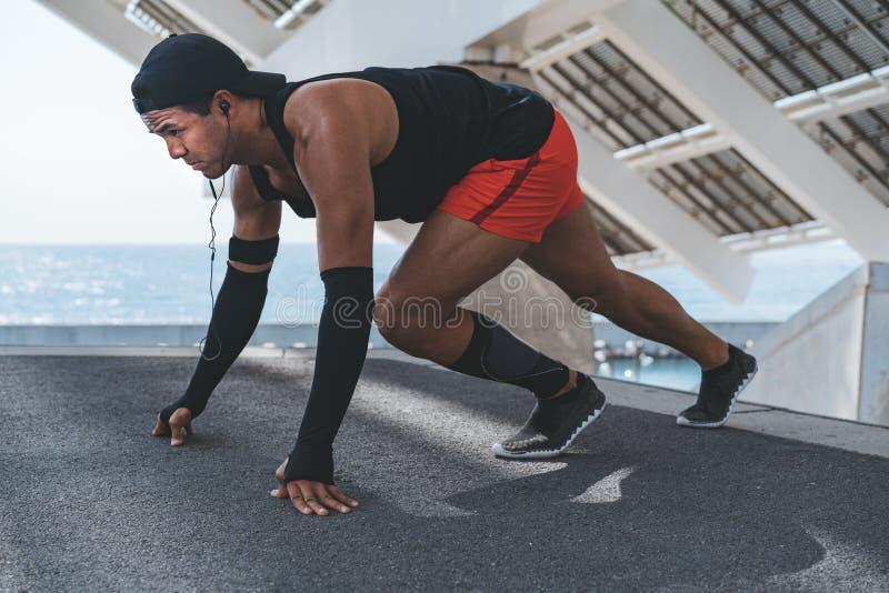 Corredor masculino que hace estirando el ejercicio, preparándose para el entrenamiento de la mañana al aire libre imagenes de archivo
