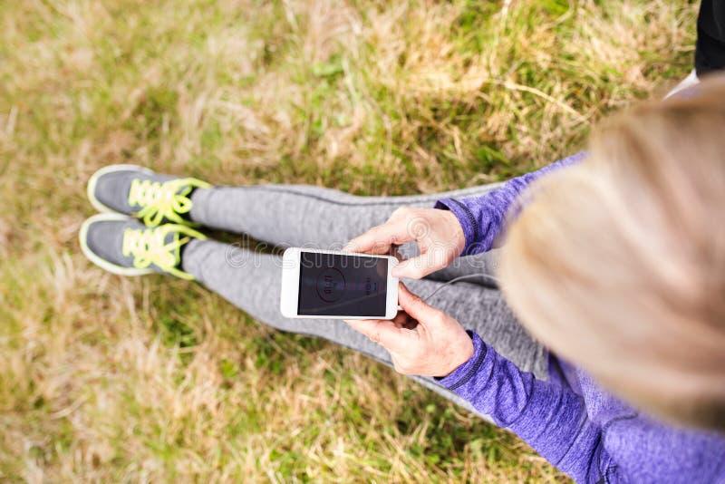 Corredor mayor activo irreconocible en naturaleza con el teléfono elegante foto de archivo