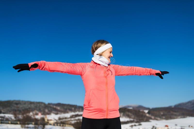 Corredor mayor de la mujer que estira en naturaleza del invierno Copie el espacio fotos de archivo