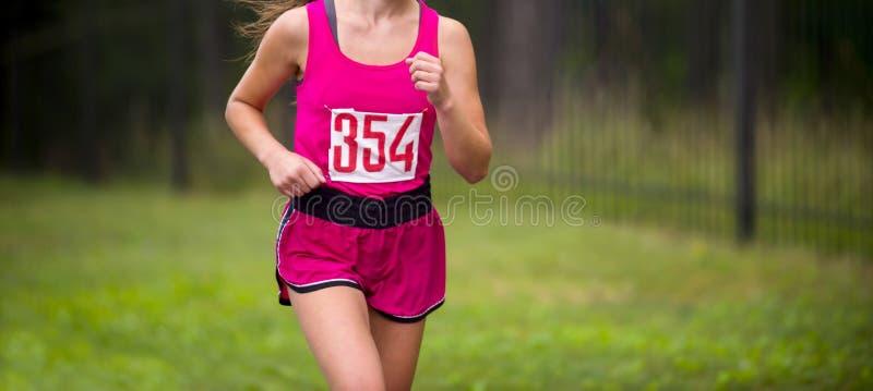 Corredor novo da mulher da aptidão que corre na estrada menina que prepara o herse foto de stock