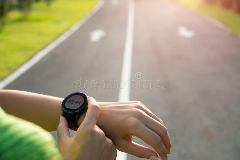Corredor novo da mulher da aptidão que estabelece o relógio esperto antes de correr o treinamento durante o por do sol Conceito e fotografia de stock