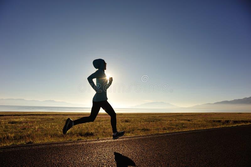 Corredor novo da mulher da aptidão que corre na fuga do beira-mar do nascer do sol imagens de stock royalty free