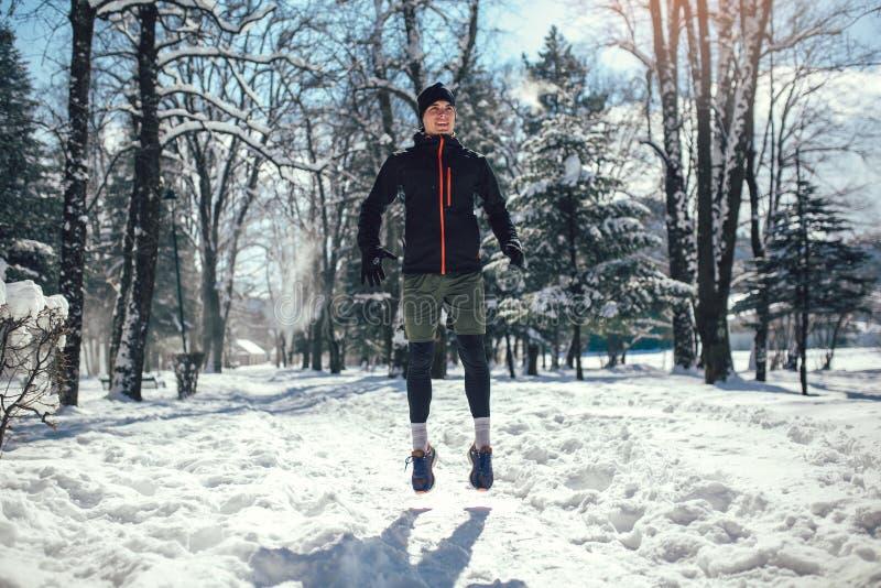 Corredor novo no sportswear que salta na estrada coberto de neve do inverno imagens de stock