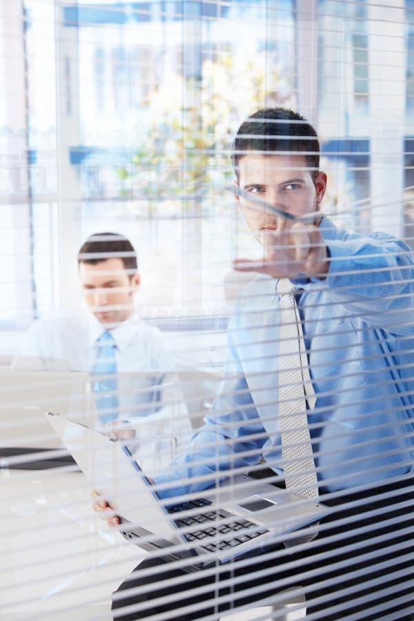 Corredor novo peeping do homem de negócios através das cortinas fotografia de stock