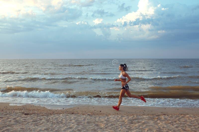 Corredor novo saudável da fuga da mulher da aptidão que corre no beira-mar do nascer do sol fotografia de stock royalty free