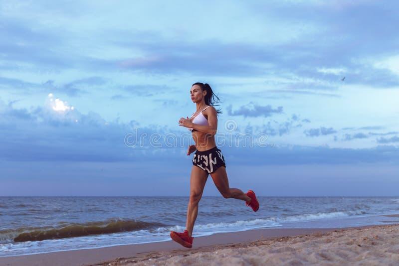 Corredor novo saudável da fuga da mulher da aptidão que corre no beira-mar do nascer do sol imagem de stock