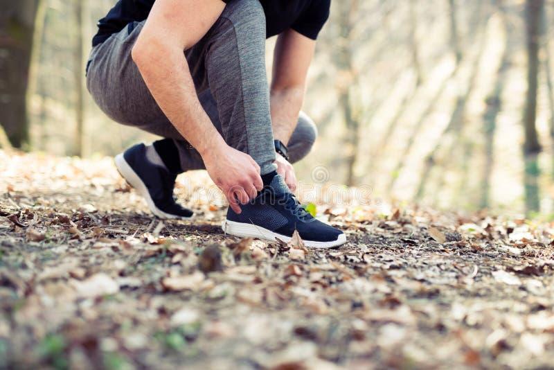Corredor que amarra suas sapatas que preparam-se para um movimento imagens de stock