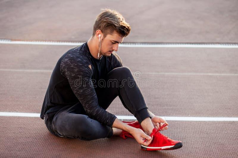 Corredor que consigue cordones de zapatillas deportivas que atan que activan listos mientras que se sienta en pista fotos de archivo