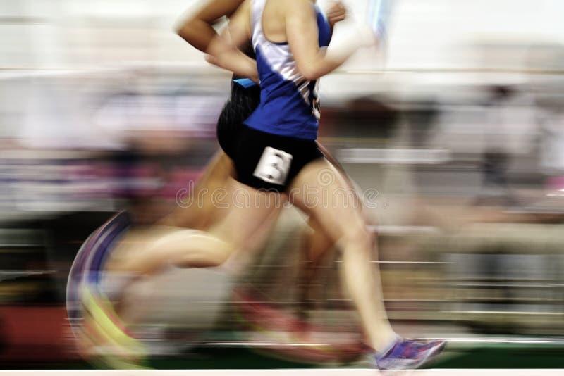 Corredor que corre una carrera en pista con la retransmisión Team Score del bastón imagen de archivo libre de regalías