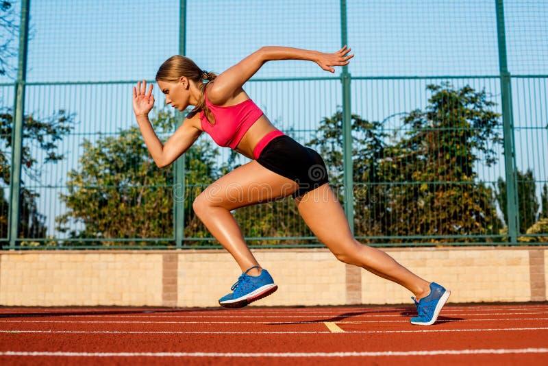 Corredor que esprinta hacia éxito en la trayectoria funcionada con que corre la pista atlética Concepto del logro de la meta fotos de archivo