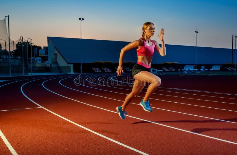 Corredor que esprinta hacia éxito en la trayectoria funcionada con que corre la pista atlética Concepto del logro de la meta foto de archivo