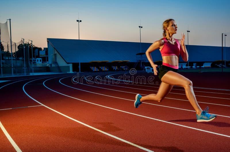Corredor que esprinta hacia éxito en la trayectoria funcionada con que corre la pista atlética Concepto del logro de la meta imágenes de archivo libres de regalías