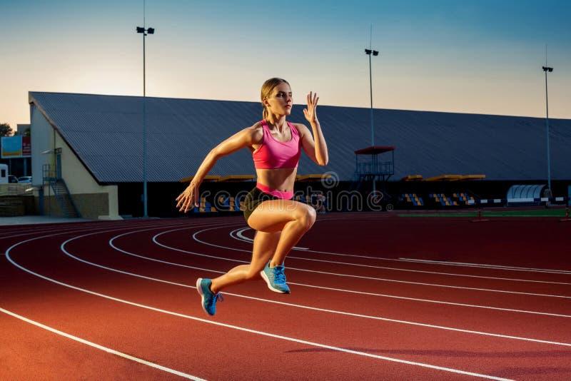 Corredor que esprinta hacia éxito en la trayectoria funcionada con que corre la pista atlética Concepto del logro de la meta imagen de archivo libre de regalías