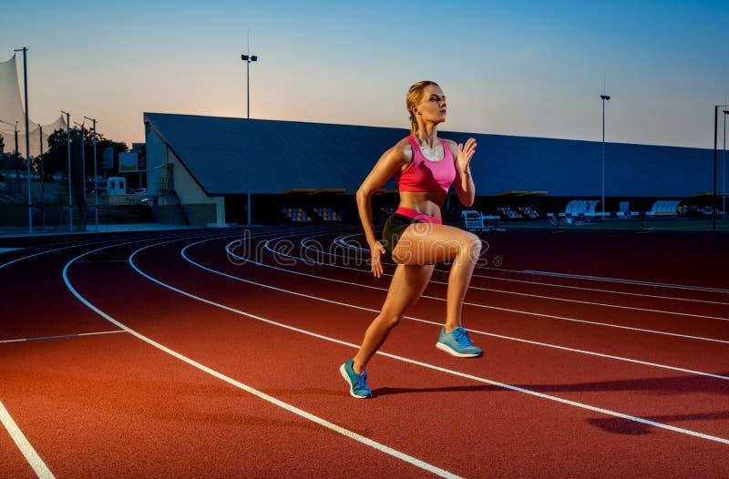 Corredor que esprinta hacia éxito en la trayectoria funcionada con que corre la pista atlética Concepto del logro de la meta fotos de archivo libres de regalías
