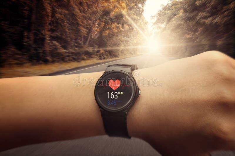 Corredor que verifica no relógio do monitor da frequência cardíaca que corre na estrada em f fotos de stock royalty free