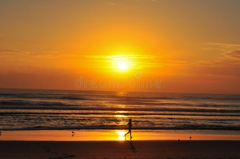 Corredor solitario de la salida del sol en la playa del paraíso de las personas que practica surf imagenes de archivo
