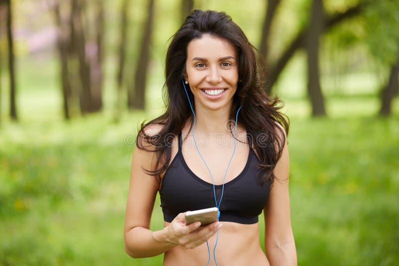Corredor sonriente de la mujer que escucha la música en el teléfono elegante foto de archivo libre de regalías