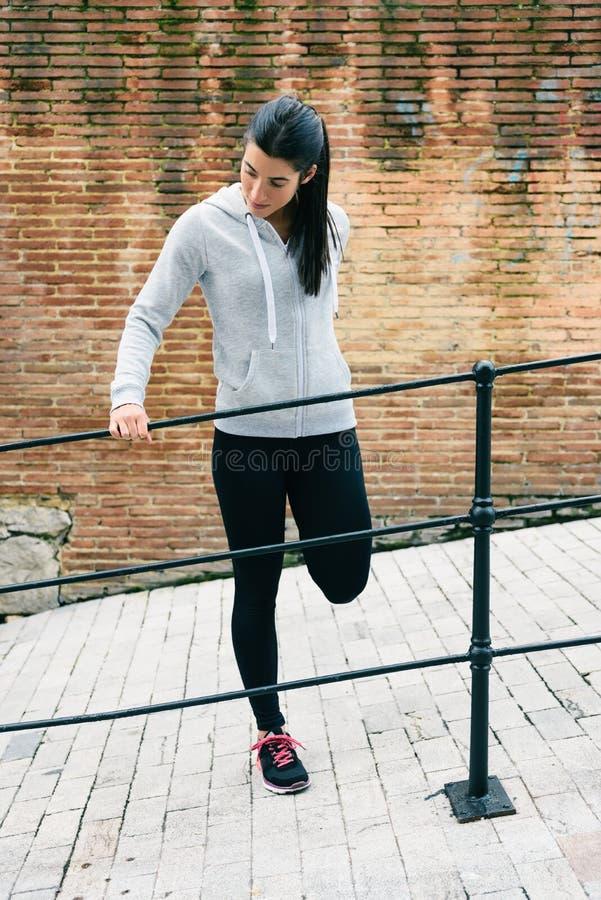 Corredor urbano femenino que estira las piernas antes de correr imagen de archivo libre de regalías