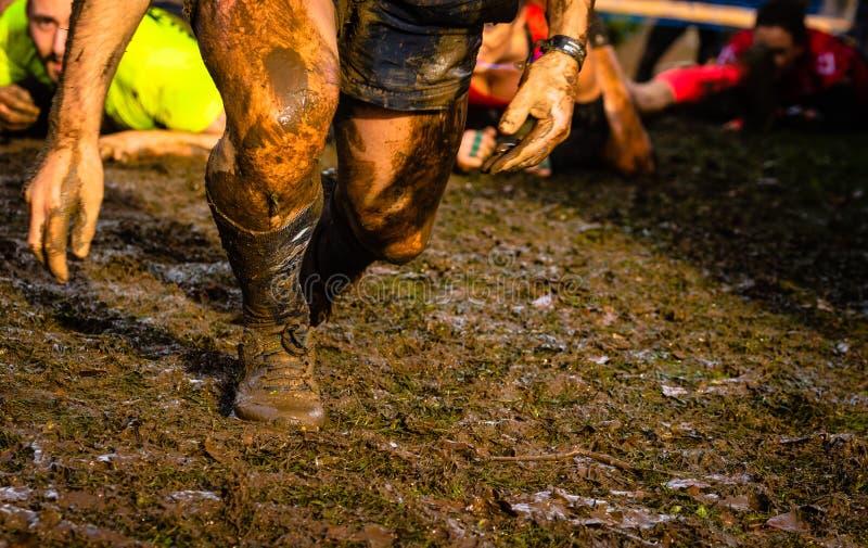 Corredores de raça da lama que passam sob obstáculos de um arame farpado durante a raça de obstáculo extrema foto de stock