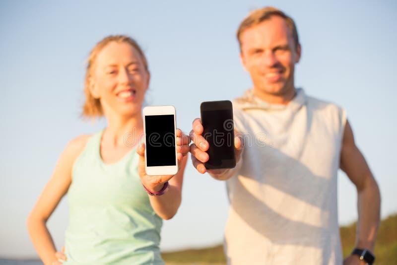 Corredores en la playa que sostiene sus smartphones foto de archivo libre de regalías