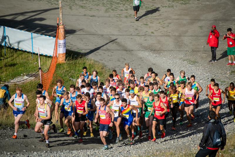 Corredores encima de la primera colina en la raza de campeonatos de funcionamiento de la montaña del mundo fotografía de archivo