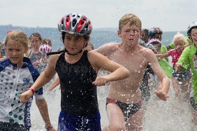 Corredores júniors do triathlon em séries de Mudman do aQuelle foto de stock royalty free