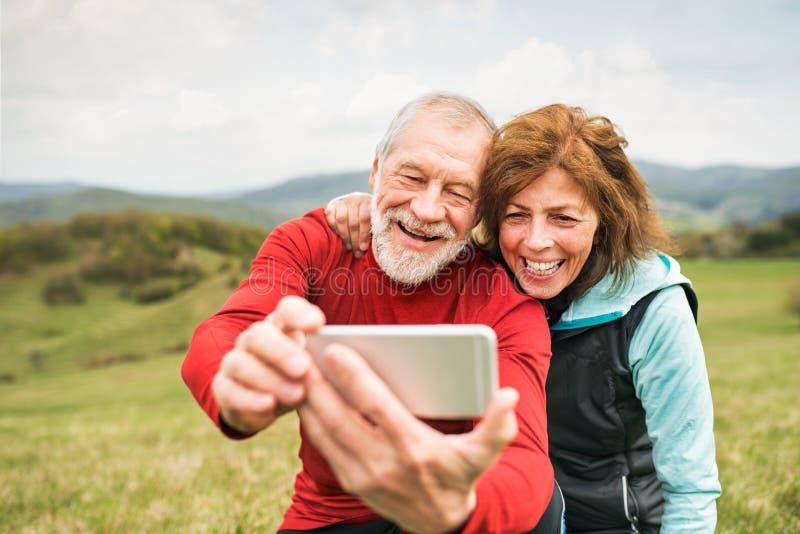 Corredores mayores activos en la naturaleza que toma la foto con el teléfono elegante foto de archivo libre de regalías