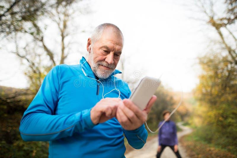 Corredores mayores en la naturaleza, estirando Hombre con smartphone con e imagen de archivo libre de regalías