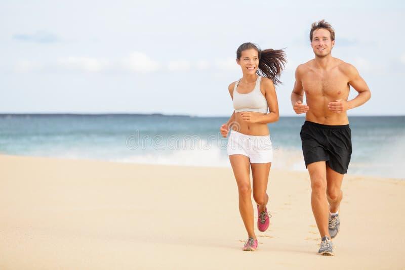 Corredores - pares jovenes que corren en la playa foto de archivo