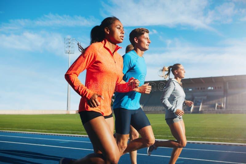 Corredores que corren en circuito de carreras en estadio imágenes de archivo libres de regalías