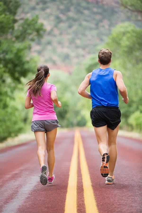 Corredores running do treinamento que movimentam-se na estrada imagem de stock royalty free