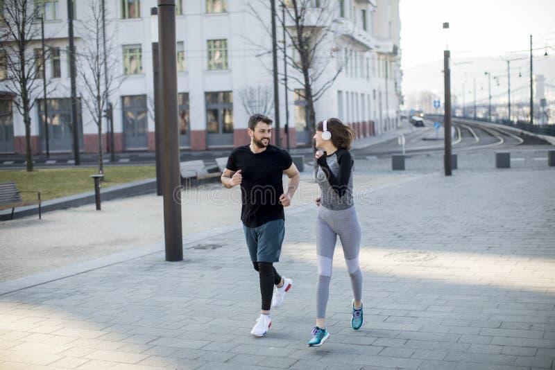 Corredores sanos que corren en ciudad con paisaje urbano en fondo fotografía de archivo libre de regalías