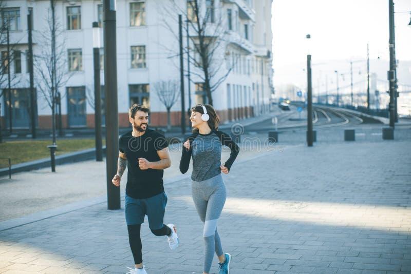 Corredores sanos que corren en ciudad con paisaje urbano en fondo imagen de archivo