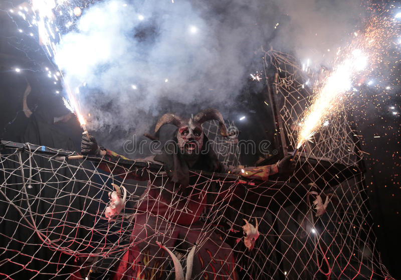 Correfoc sant sebastian 021. Men dressed as devils or evil hords and holding sticks with fireworks seen during a correfoc in the spanish island of mallorca stock photography