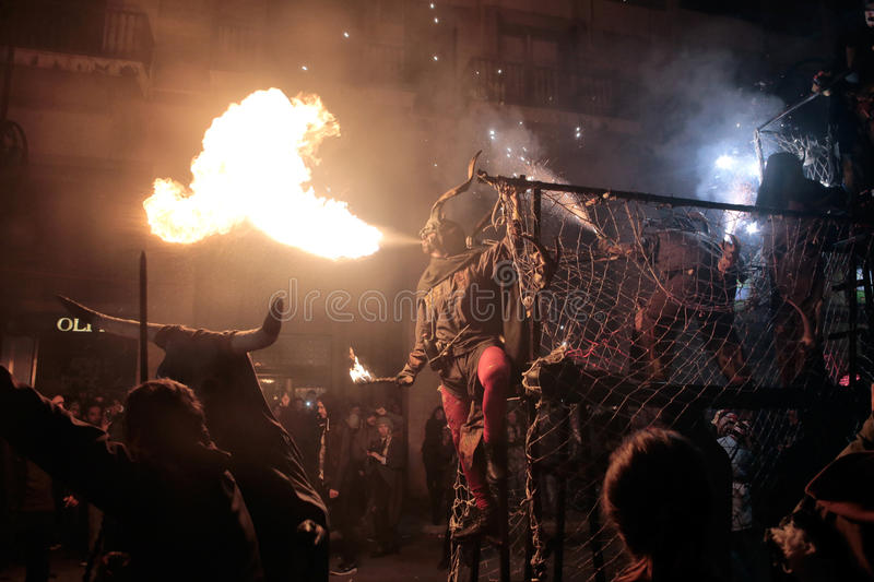 Correfoc sant sebastian 020. Men dressed as devils or evil hords and holding sticks with fireworks or spitting fire with their mouths seen during a correfoc in stock image