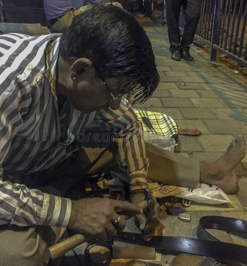 Correia de cintura dos reparos do homem na rua imagens de stock royalty free